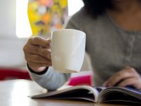 a girl is drinking coffee and reading a magazine.